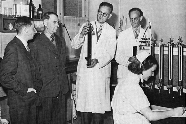 Jörgen Lehmann demonstrerar en Warburgmikrorespirometer som användes för att studera tuberkelbakteriernas respiration. Fotot togs under det 13:e Nordiska Tuberkulosläkarmötet i Göteborg den 26-27 juni 1946. Från vänster: Ingenjör Rosdahl, överläkare Vallentin, Jörgen Lehmann, Dr. Sievers och syster Elisabeth Rydell.