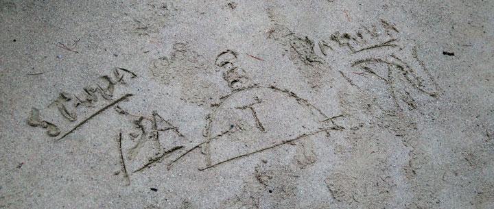 Guiden ritade buddhistiska världsbilden i den våta sanden.