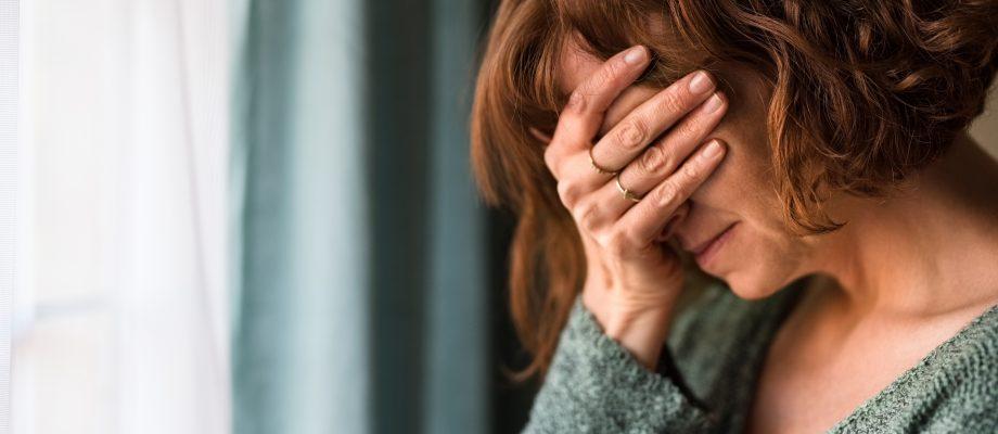 Kvinna står vid ett fönster med handen över ögonen. Hon ser ut att vara trött och sjuk.